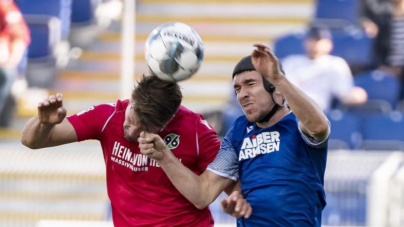 Der Hannoveraner Hendrik Weydandt und der Karlsruher Damian Roßbach (l-r.) kämpfen um den Ball. Foto: Uli Deck/dpa