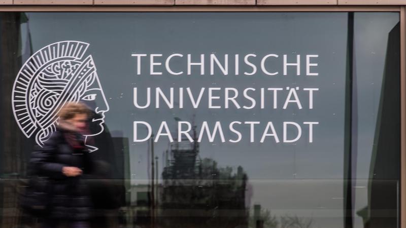 Eine Frau vor einer Glasfassade der Technischen Universität Darmstadt. Foto: Andreas Arnold/dpa/Archivbild