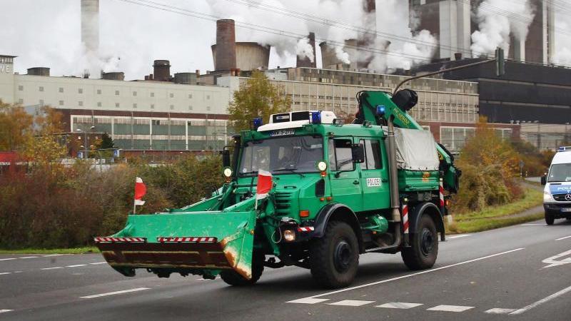 Einsatzfahrzeuge der Polizei fahren zum Gelände des Braunkohlekraftwerkes Weisweiler bei Aachen. Foto: Ralf Roeger/Archivbild