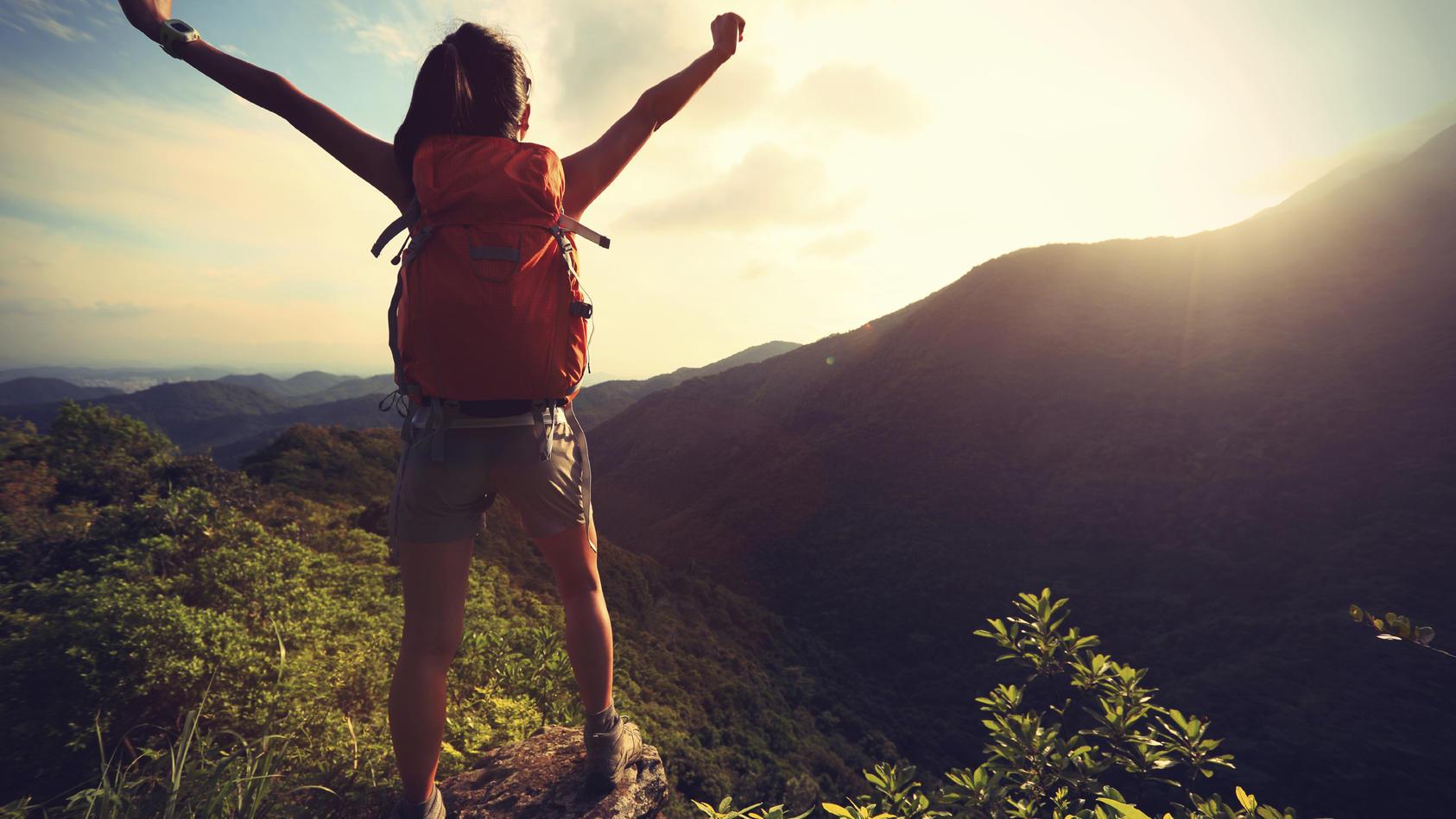 Rucksack-Touristen steht jubelnd an einem Berg im Sonnenlicht