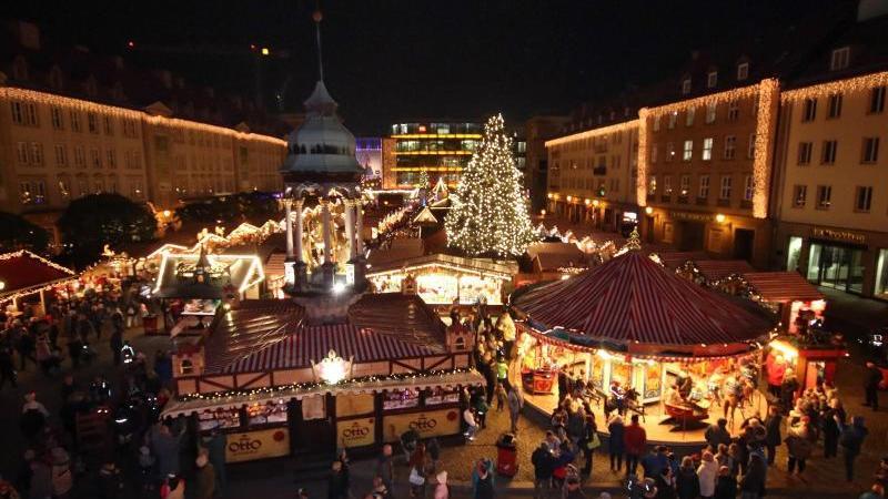 Besucher gehen über den Weihnachtsmarkt, der auf dem Alten Markt vor dem Alten Rathauses stattfindet. Foto: Peter Förster/zb/dpa