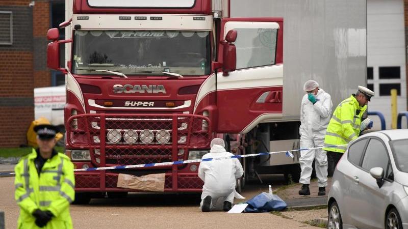 Polizisten und Mitarbeiter der Spurensicherung arbeiten an dem LKW, in dem 39 Leichen gefunden wurden. Foto: Stefan Rousseau/PA Wire/dpa