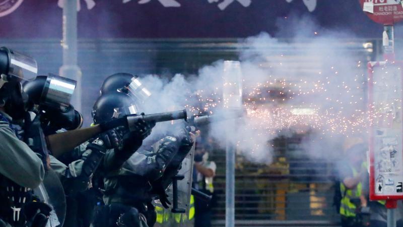 Polizisten mit Gasmasken schießen Tränengas auf Demonstranten. Foto: Dita Alangkara/AP/dpa