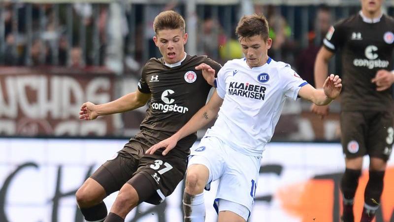 Hamburgs Finn Ole Becker (l.) und Marvin Wanitzek von Karlsruhe kämpfen um den Ball. Foto: Daniel Bockwoldt/dpa