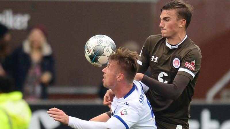 Karlsruhes Marvin Pourie (l.) und Hamburgs Philipp Ziereis kämpfen um den Ball. Foto: Daniel Bockwoldt/dpa