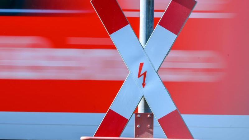 Ein Andreaskreuz steht an einem Bahnübergang. Foto: Jens Büttner/dpa-Zentralbild/dpa/Archivbild