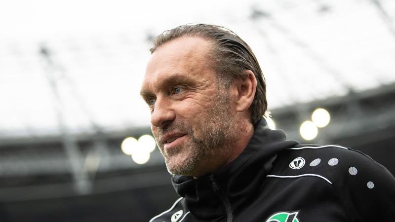 Hannovers Ex-Trainer Thomas Doll steht vor einem Spiel am Spielfeldrand. Foto: Swen Pförtner/dpa/Archivbild