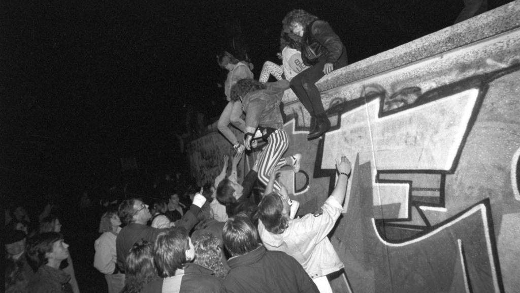 ARCHIV - 09.11.1989, Berlin: Menschen klettern am späten Abend auf die Berliner Mauer am Brandenburger Tor. Am Abend des 09.11.1989 teilte SED-Politbüro Mitglied Schabowski mit, daß alle DDR-Grenzen in die Bundesrepublik und nach West-Berlin für DDR-