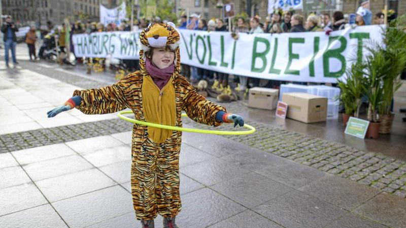 Ein Kind tanzt mit einem Reifen vor Teilnehmern einer Nabu-Aktion zum Erhalt des Vollhöfner Waldes. Foto: Axel Heimken/dpa/Archivbild