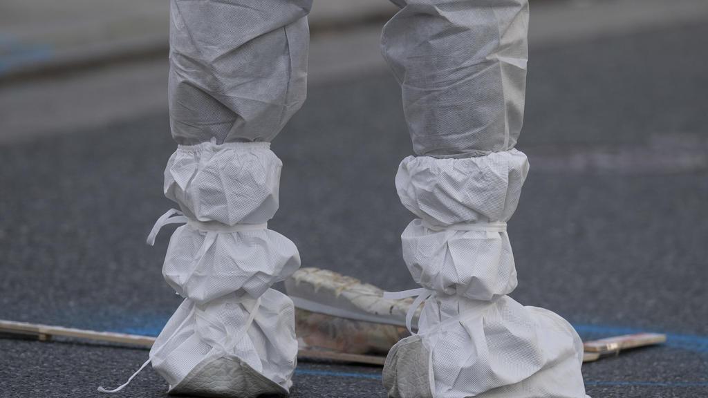25.10.2019, Hessen, Limburg An Der Lahn: Eine Mitarbeiterin der Spurensicherung dokumentiert einen Schuh, der nach der Tötung einer Frau in der Innenstadt auf der Straße liegt. Nach bisherigen Ermittlungen der Polizei hatte ein 34-jähriger Mann seine