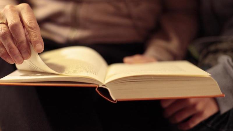Eine Mutter liest in einem Buch. Foto: Hans-Thomas Frisch/dpa