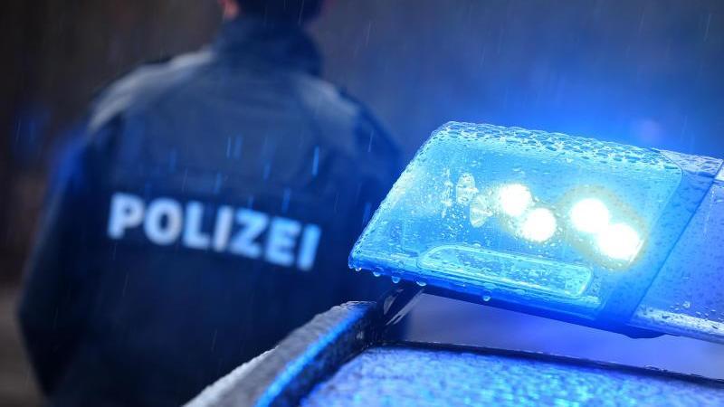 Ein Polizist steht im Regen vor einem Streifenwagen dessen Blaulicht aktiviert ist. Foto: Karl-Josef Hildenbrand/dpa