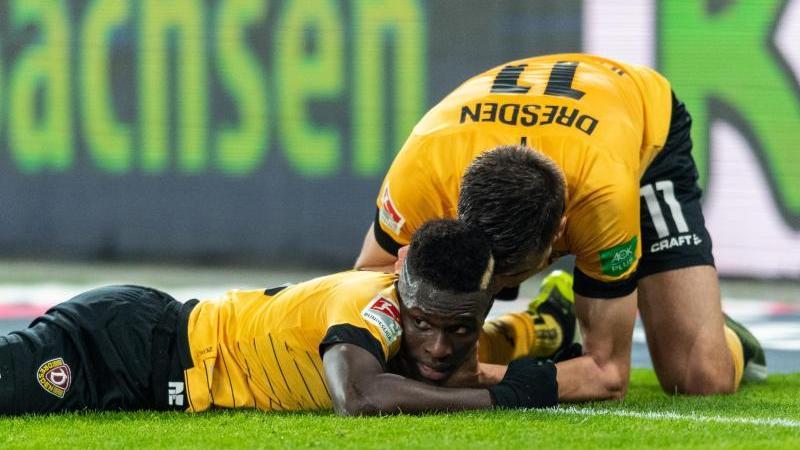 Moussa Kone (l) feiert mit Dynamo-Torschütze Alexander Jeremejeff. Foto: Robert Michael/dpa-Zentralbild/dpa