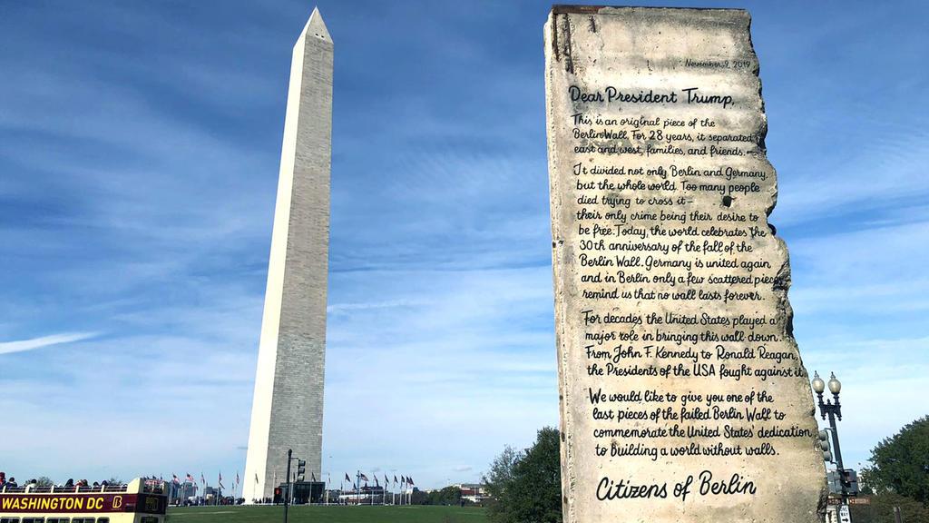 HANDOUT - 09.11.2019, USA, Washington: Ein Segment der Berliner Mauer mit einem Text an US-Präsident Trump steht vor dem Obelisken. Zum 30. Jahrestag des Mauerfalls wurde das 2,7 Tonnen schwere Originalsegment vor das Weiße Haus gekarrt, wo es abgege