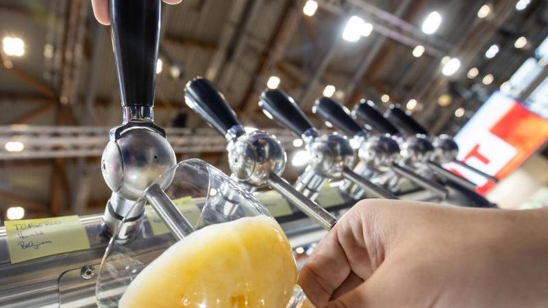 """Ein Mitabreiter eines Stands auf der Getränkemesse """"BrauBeviale"""" zapft ein Bier. Foto: Daniel Karmann/dpa/Archivbild"""