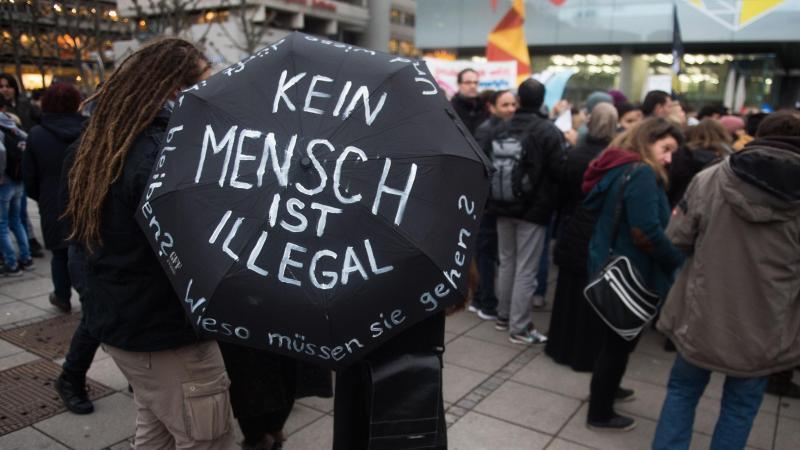 """Eine Frau hält während einer Demonstration einen Regenschirm mit der Aufschrift """"Kein Mensch ist illegal"""". Foto: Lino Mirgeler/dpa/Archivbild"""