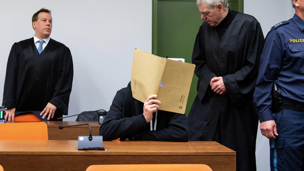 München: Der wegen versuchten Mordes an zahlreichen Frauen und Mädchen 30-jährige Angeklagte kommt vor Prozessbeginn im Landgericht zusammen mit seinen Anwälten in den Sitzungssaal.
