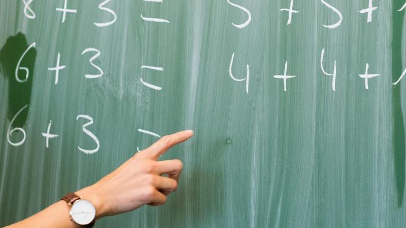 Eine Lehrerin zeigt in einer Schule an eine Tafel. Foto: Julian Stratenschulte/dpa/Archivbild