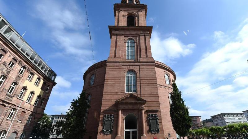 Touristen stehen vor der Paulskirche. Foto: Arne Dedert/Archiv
