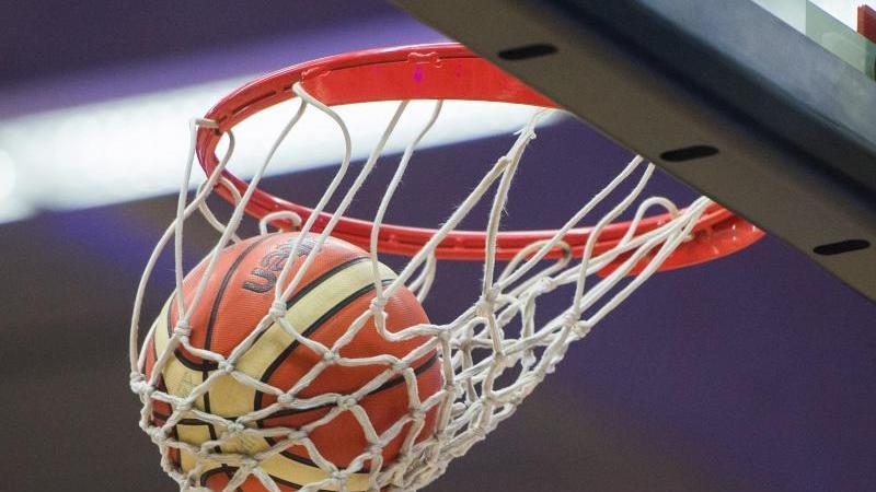 Ein Basketball fällt in den Basketballkorb. Foto: Lukas Schulze/dpa