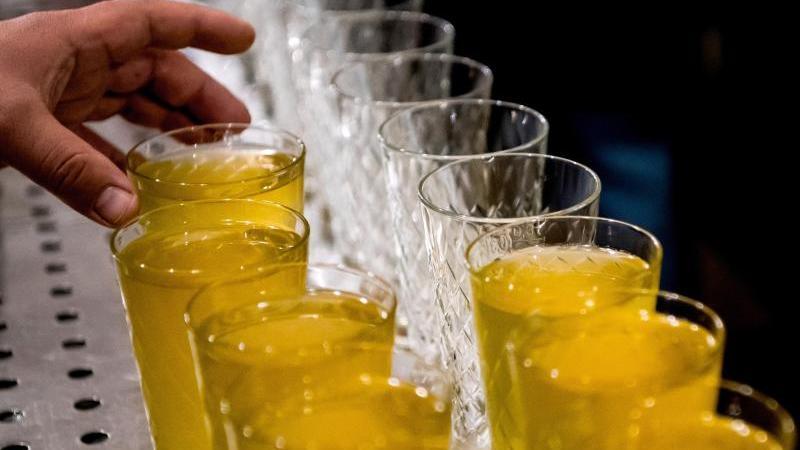 Eine Hand greift nach einem Apfelwein-Glas. Foto: Andreas Arnold/dpa