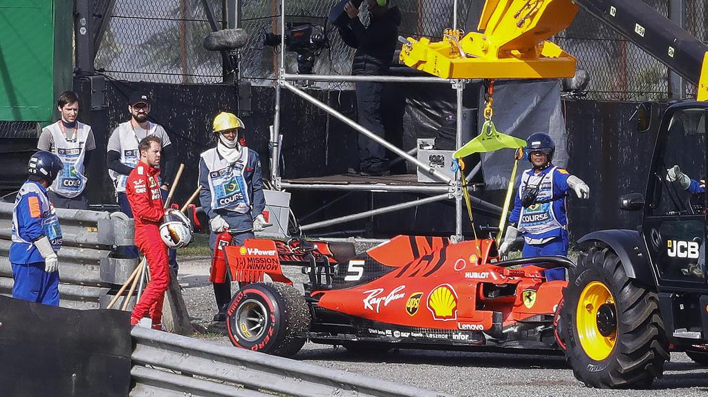 17.11.2019, Brasilien, Sao Paulo: Motorsport: Formel-1-Weltmeisterschaft, Grand Prix von Brasilien, Rennen: Sebastian Vettel (4.v.l) aus Deutschland vom Team Ferrari steht neben seinem Rennenwagen nach einem Unfall mit seinem Teamkollegen Leclerc. In