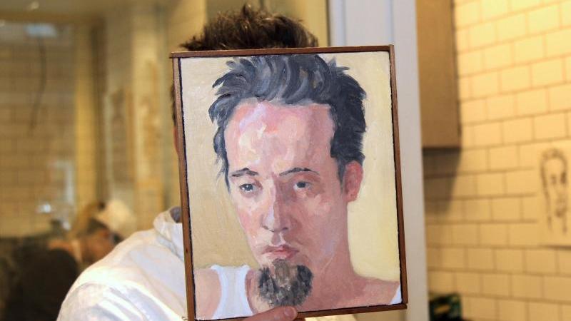 Sebastian Brecht hält sich ein Portrait vor sein Gesicht, das die Künstlerin Alix Bailey von ihm gemalt hat. Foto: Marie Weigl/dpa