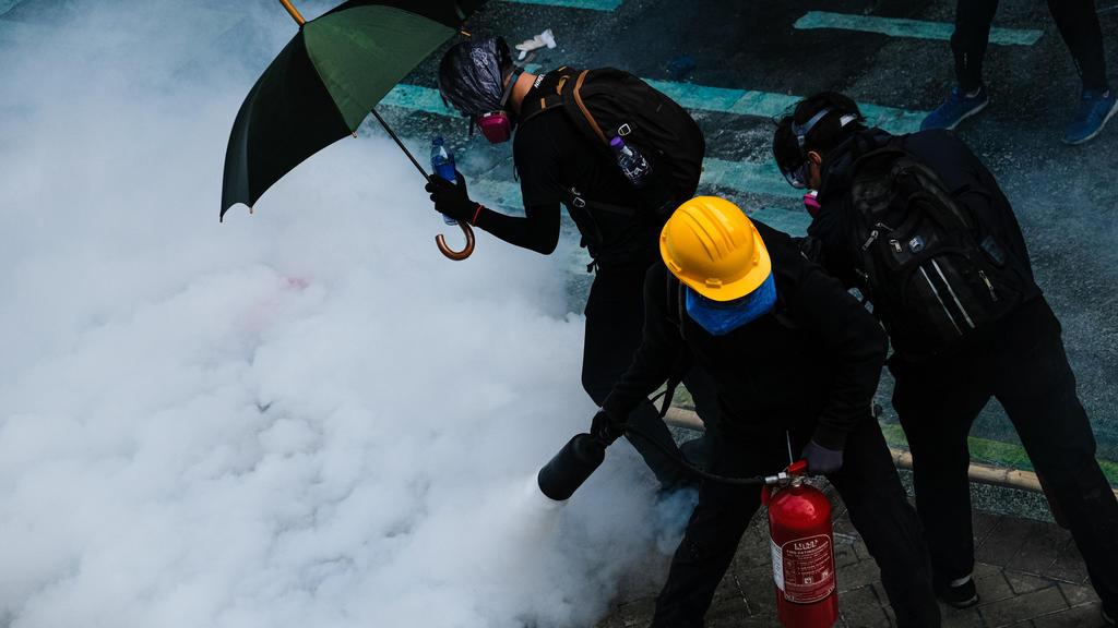 18.11.2019, China, Hongkong: Demonstranten löschen bei einem Protest in Hongkong Tränengas mit einem Feuerlöscher. Die Auseinandersetzungen zwischen Demonstranten und der Polizei gehen unvermindert weiter. Foto: Keith Tsuji/ZUMA Wire/dpa +++ dpa-Bild