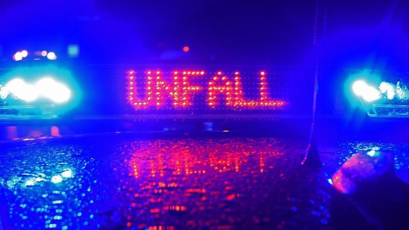 """Blaulicht und der Schriftzug """"Unfall"""" spiegeln sich auf einem Streifenwagen. Foto: Stefan Puchner/dpa/Archivbild"""