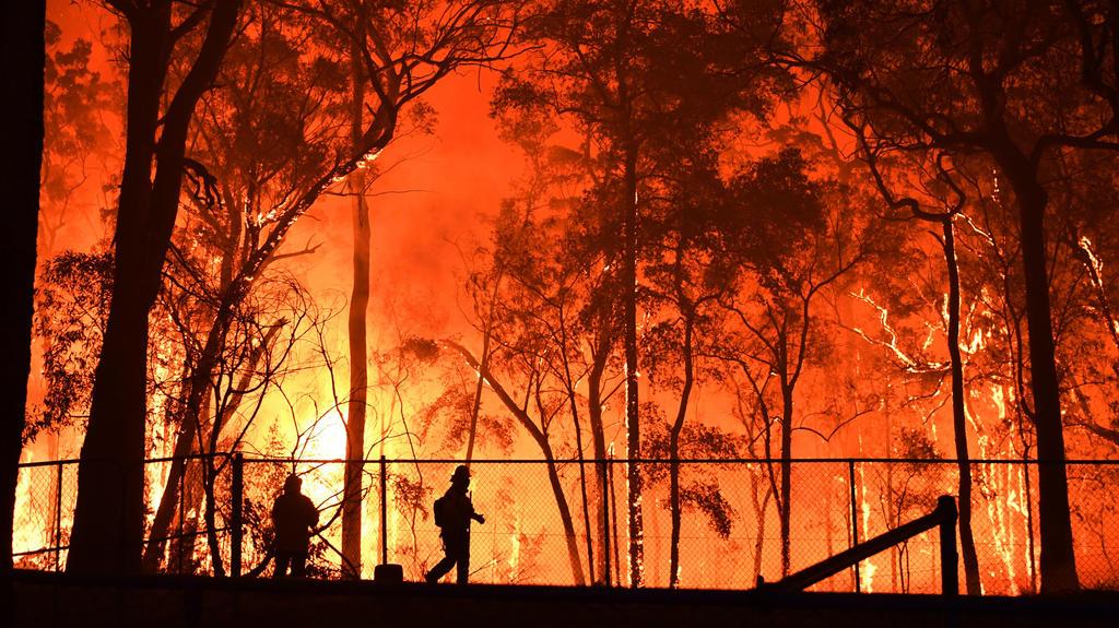 dpatopbilder - 19.11.2019, Australien, Colo Heights: Zwei Feuerwehrleute sind im Einsatz, um die Colo Heights Public School zu schützen. Wegen der Buschbrände in der Umgebung von Sydney wird die Lage auch in Australiens Millionenmetropole selbst zune