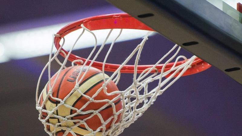 Ein Basketball fällt in den Basketballkorb. Foto: Lukas Schulze/dpa/Archivbild