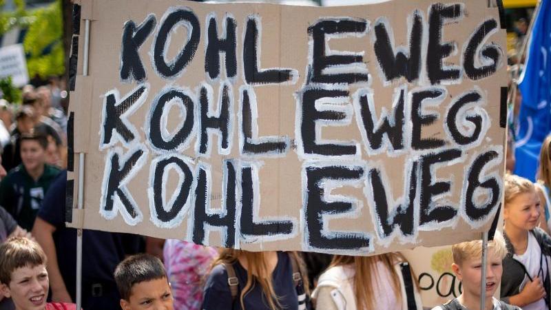 """Teilnehmer von """"Fridays for Future"""" stehen mit ihrem Transparent mit der Aufschrift """"Kohle weg"""". Foto: Monika Skolimowska/dpa-Zentralbild/ZB"""