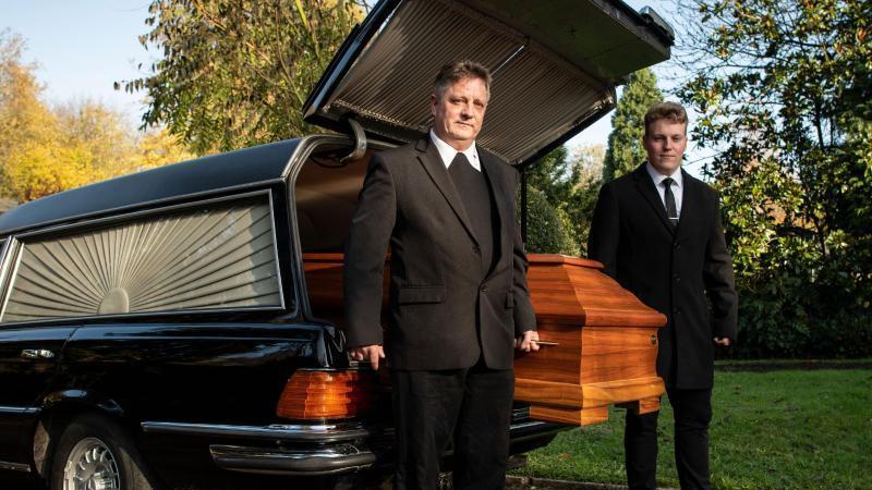Bestatter Michael Wasch und sein Sohn heben einen Sarg aus einem Leichenwagen. Foto: Bernd Thissen/dpa