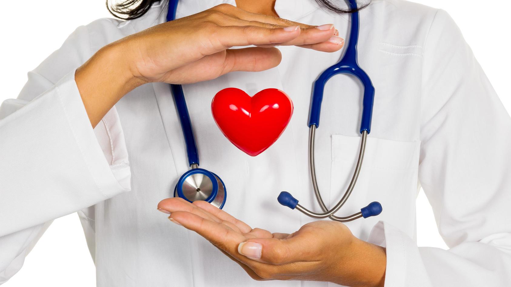 Eine junge Ärztin (Internistin) hält ein Herz symbolisch in der Hand.
