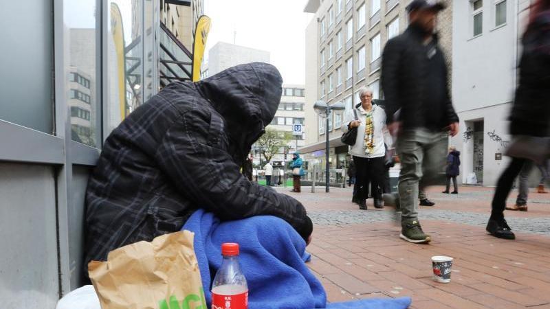 ILLUSTRATION - Ein Obdachloser sitzt in der Fußgängerzone. Foto: Ina Fassbender/dpa/Archivbild