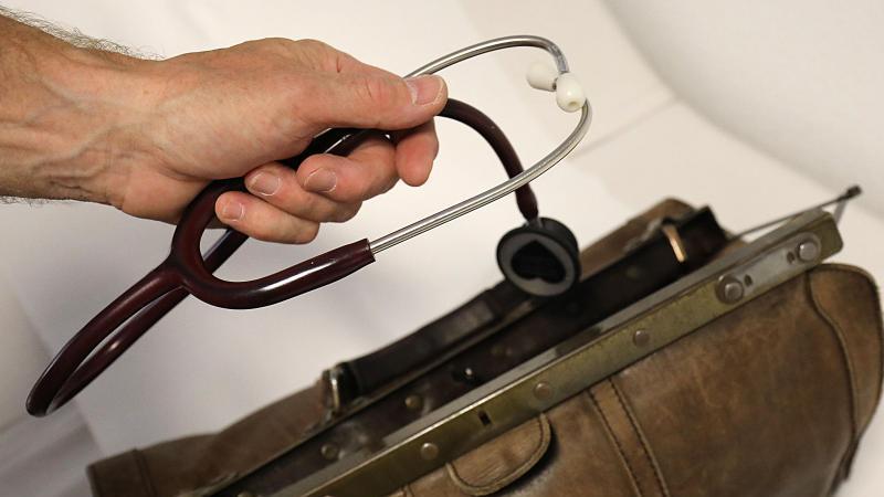 Ein Landarzt nimmt sein Stethoskop aus dem Koffer. Foto: Oliver Berg/dpa/Archivbild