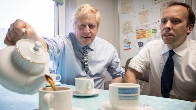 Premierminister Boris Johnson und Gesundheitsminister Matt Hancock widmen sich beim Besuch eines Krankenhauses einer britischen Tradition - dem Teetrinken. Foto: Stefan Rousseau/PA Wire/dpa