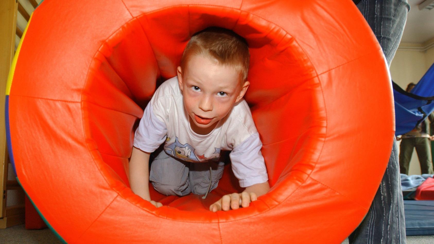 Ein Fünfjähriger kriecht während einer Psychomotorik-Stunde im Rahmen der Frühförderung für Vorschulkinder durch einen Spielzeugtunnel.
