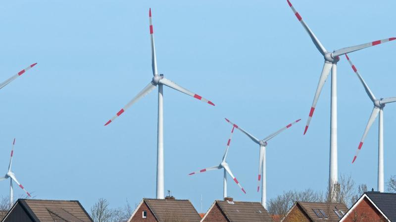 Windräder eines Windparks drehen sich dicht hinter einer Wohnsiedlung. Foto: Ingo Wagner/dpa