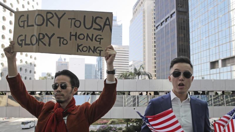 """Demonstranten halten amerikanische Flaggen und ein Plakat mit der Aufschrift """"Glory to USA, Glory to Hong Kong"""" (""""Ruhm für die USA, Ruhm für Hong Kong"""") hoch. Foto: Kin Cheung/AP/dpa"""