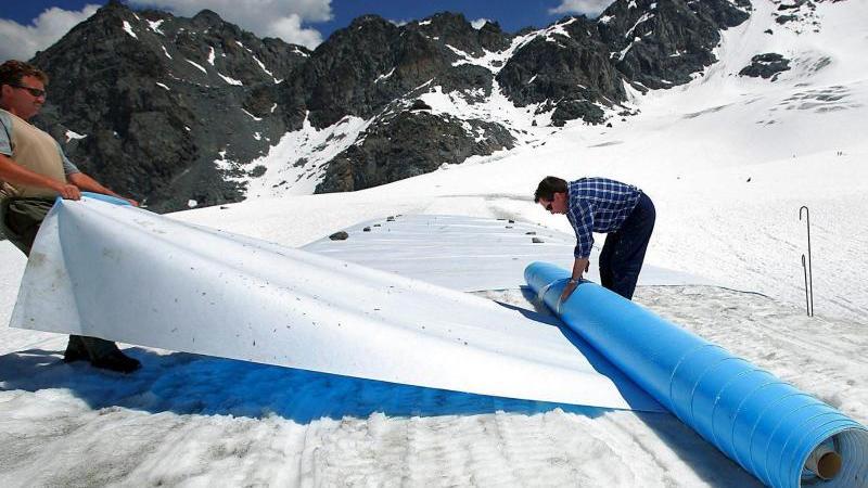 Retten, was zu retten ist:Helfer rollen im Hochsommer schützende Planen auf dem Tortin-Gletscher in der Schweiz aus. Foto: epa Keystone Olivier Maire/epa Keystone/dpa