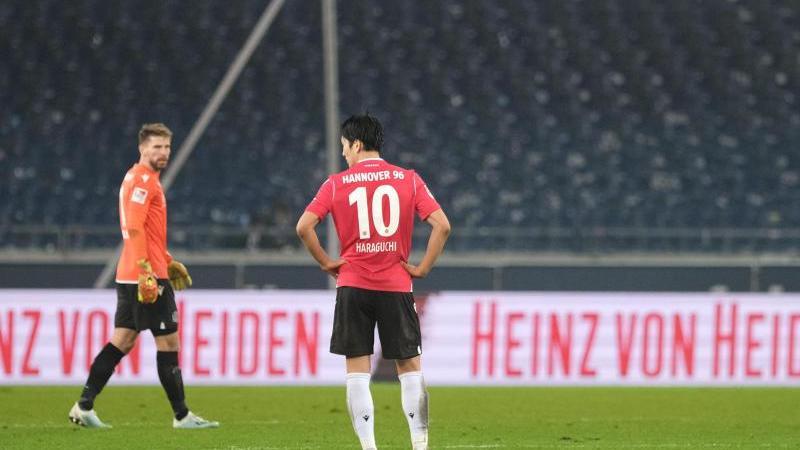 Hannovers Torwart Zieler (l-r), Haraguchi und Weydandt stehen nach dem Spiel auf dem Rasen. Foto: Peter Steffen/dpa/Archivbild