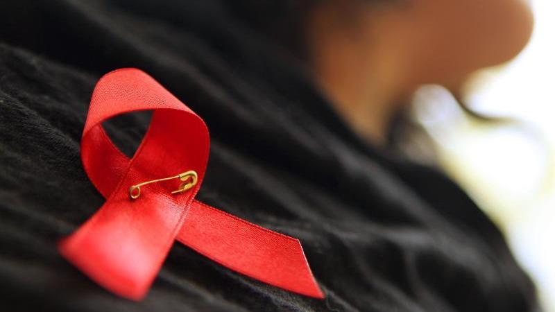 Eine Frau hat sich eine rote Schleife angeheftet. Foto: Oliver Berg/dpa