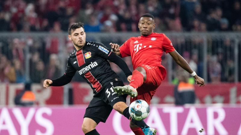 Kevin Volland von Leverkusen (l) und David Alaba vom FC Bayern München kämpfen um den Ball. Foto: Matthias Balk/dpa