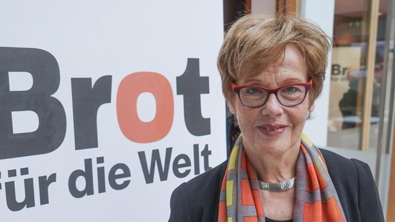 """Die Präsidentin von """"Brot für die Welt"""", steht neben dem Logo des evangelischen Hilfswerks. Foto: Jörg Carstensen/dpa"""