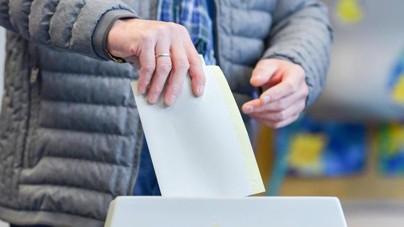 Ein Wähler wirft seinen Stimmzettel in eine Wahlurne. Foto: Uwe Anspach/dpa/Symbolbild