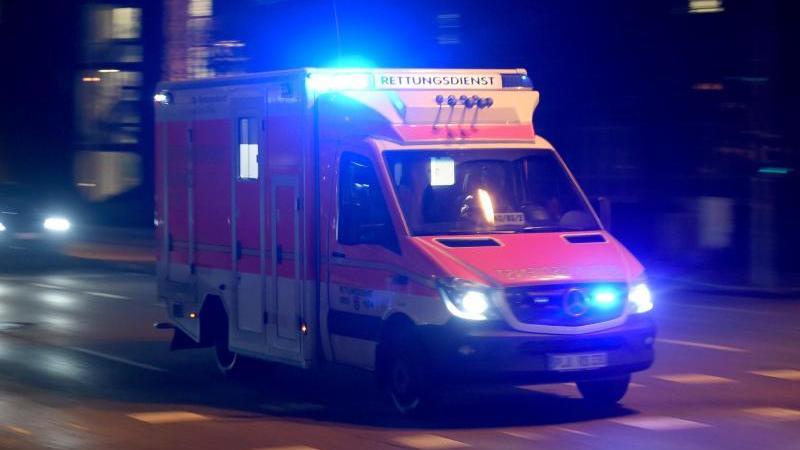 Ein Rettungswagen fährt abends mit Blaulicht über die beleuchtete Straße. Foto: Carsten Rehder/dpa/Archivbild