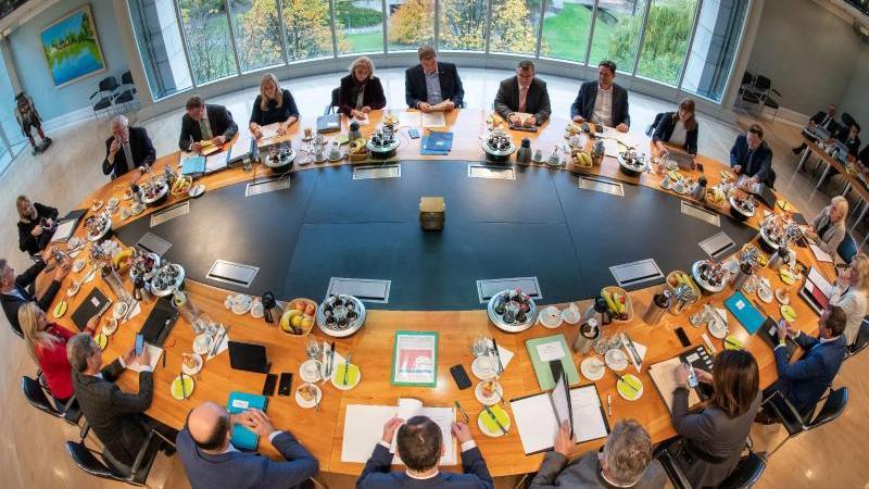 Mitglieder des bayerischen Kabinetts sitzen in der bayerischen Staatskanzlei auf ihren Plätzen. Foto: Peter Kneffel/dpa/Archivbild