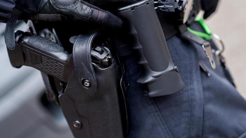 Ein Beamter trägt die Dienstwaffe am Gürtel. Foto: Hauke-Christian Dittrich/dpa