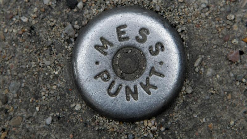 """Ein Vermessungs-Kontrollpunkt mit der Aufschrift """"Messpunkt"""" ist im Boden eingelassen. Foto: Fredrik von Erichsen/dpa/Archivbild"""